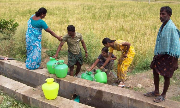 Villagers collecting borewell water from a private farmland (Source: IWP Flickr photos)
