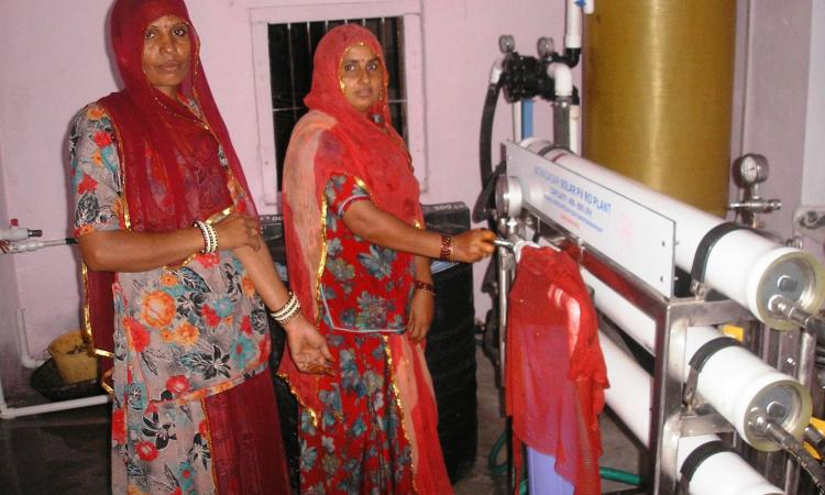 Villagers operate the solar-powered reverse osmosis desalination plant that provides safe drinking water to the community at Solawata.